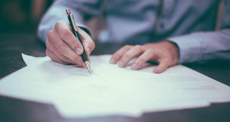 Homem a escrever a carta de encerramento da conta bancária
